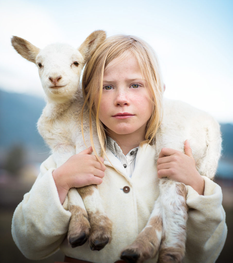 young girl poses with lamb on farm in colorado