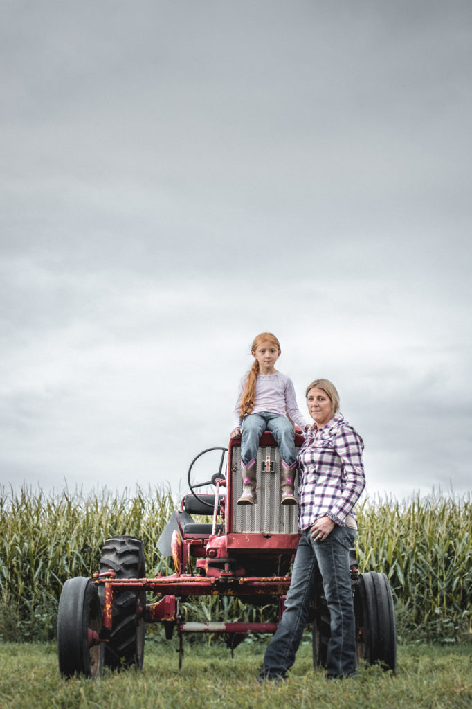 female farmers pose in field on front of tractor