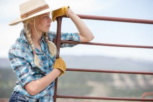 A Young Female Farmer is Photographed with her Work Gloves Leaning on a Fence. Colorado Organic Farmer Portraits.