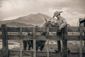 This Fine-Art Photograph is in a Series of Western Lifestyle Portraits by Tyler Stableford. Black and White of a Cowboy and his Horse in front of Mt Sopris.