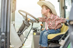 A young boy shows his excitement about driving a tractor on his family's organic farm.