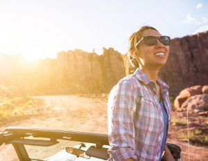 Woman IN Jeep Wrangler In Desert In Moab Utah During Summer Sunset For Lifestyle Photography Campaign.