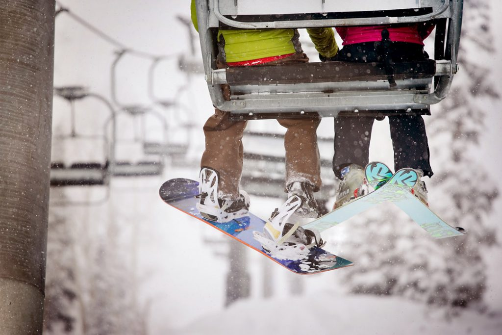Skier and Snowboarder Riding Chairlift In Aspen Colorado On A Power Day
