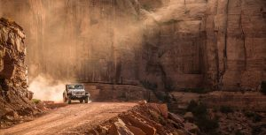 Jeep Wrangler In The Desert Of Moab Utah Driving Down A Dirt Road As The Sun Sets.