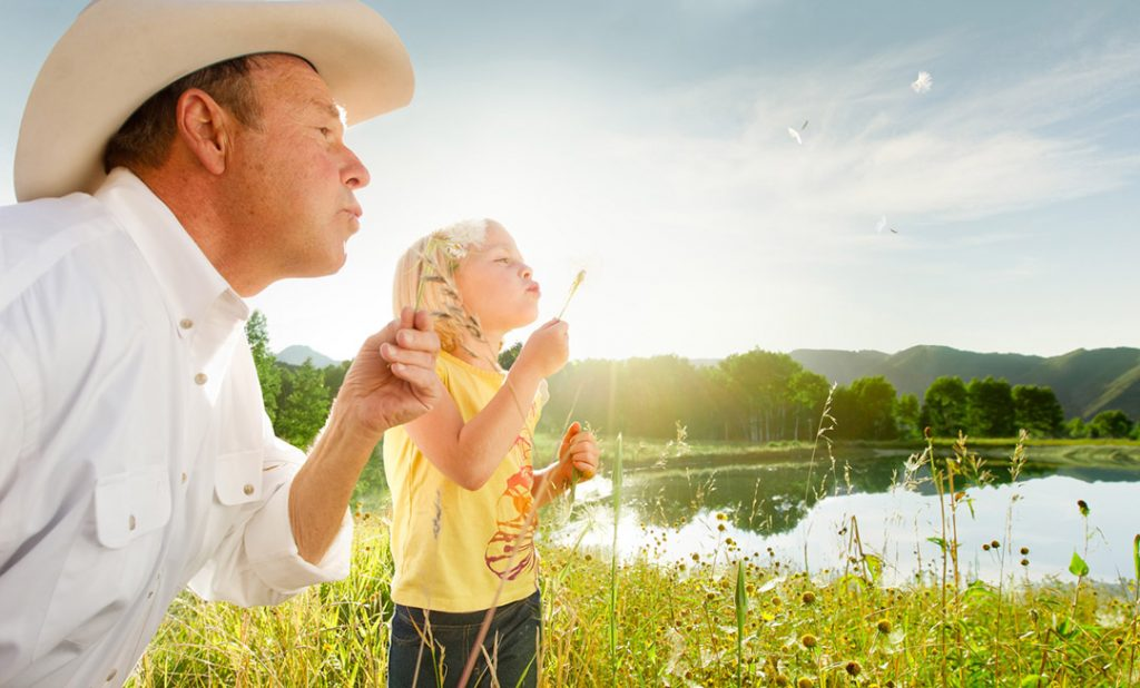 Father Daughter Blowing Flowers In A Field Near Colorado Mountains