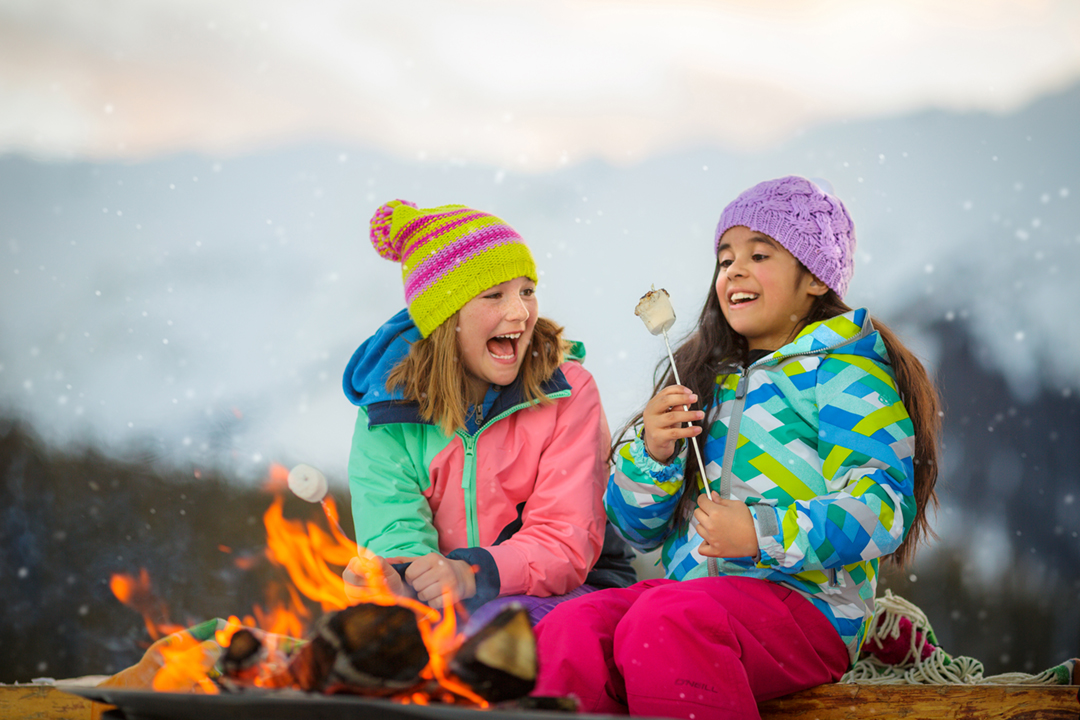 Girls Roast S'Mores at a Fire In Snowmass Colorado Shot By Tyler Stableford For Aspen Snowmass Tourism Campaign In Winter.