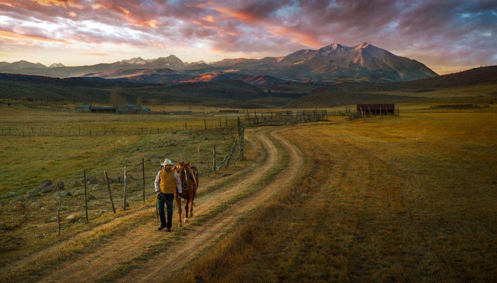A Cowboy Walks His Horse Down A Road At Sunset.