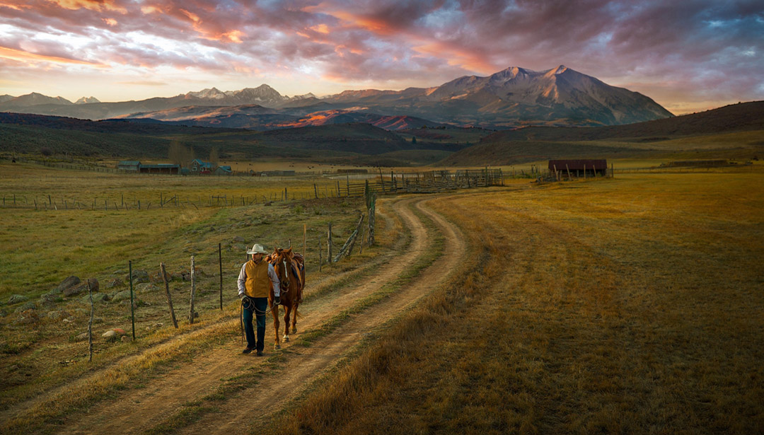 A Cowboy Walks His Horse Down A Road At Sunset.