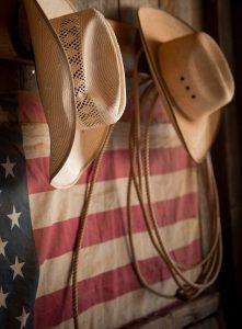 Cowboy Hats Hang By American Flag