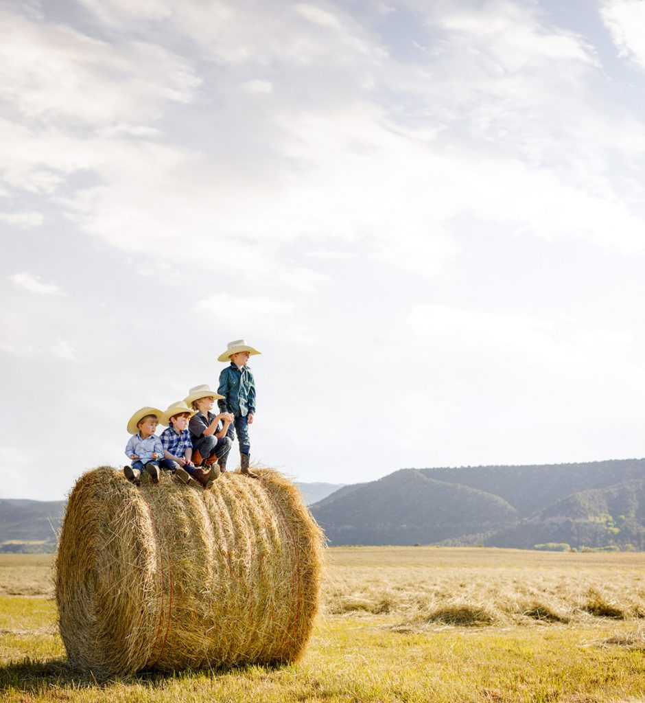 Young Farmers On A Hay Bail In The Field.