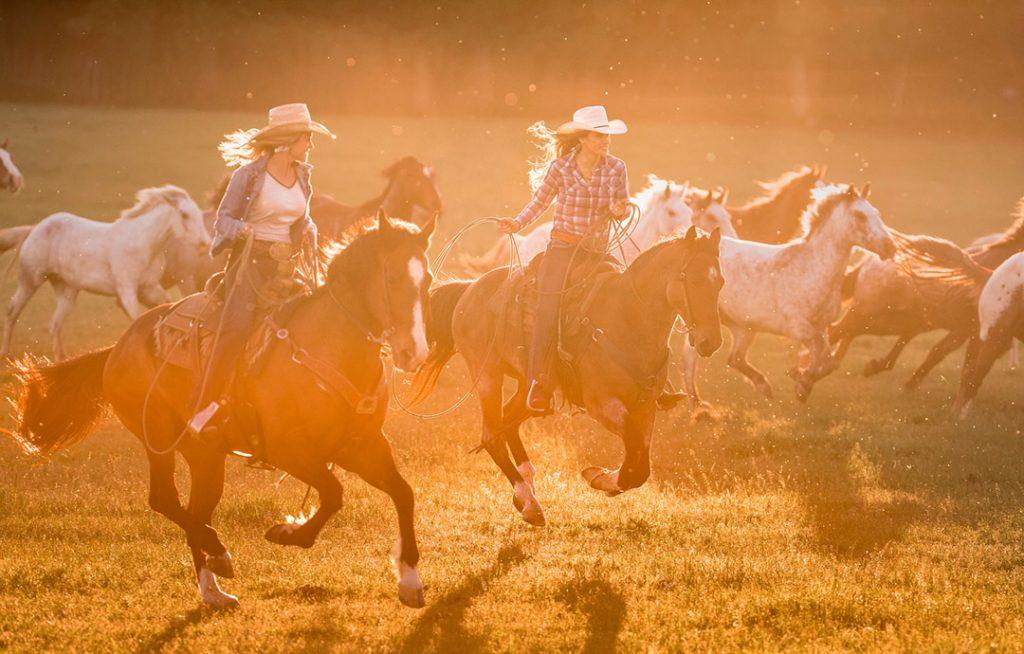 Women Ride Horses Through The Setting Sun