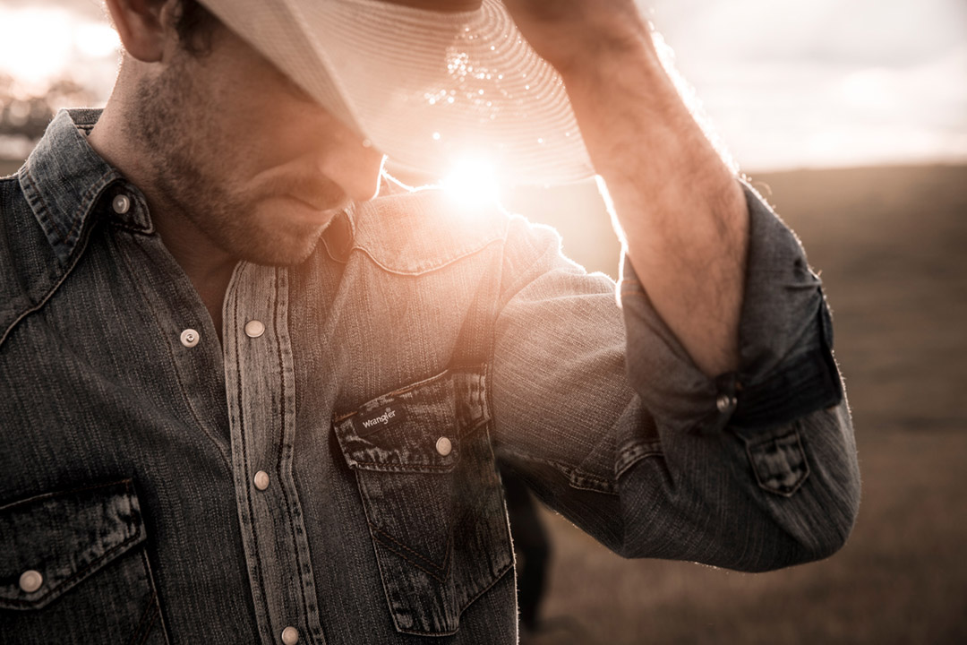 A Cowboy Adjusts His Hat As The Sun Sets