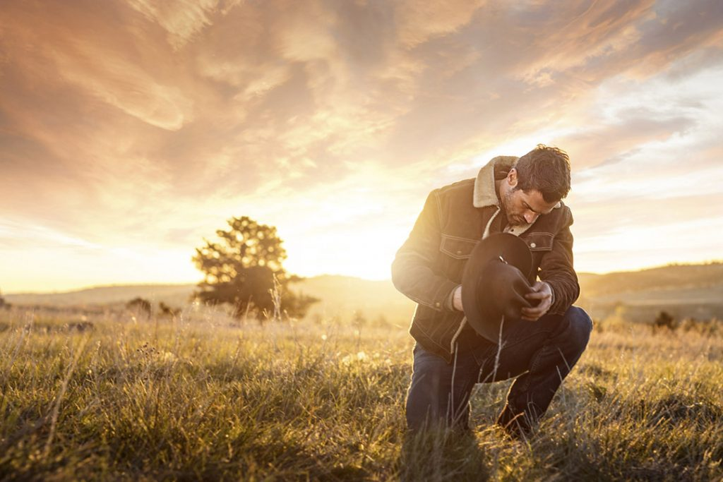 Iconic Cowboy In Field At Sunset