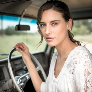 A Woman Modeling Classic Western Wear, Wrangler Brand, Sits in the Cab of a Vintage Truck on a Farm in Colorado Near Aspen.