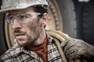 This Professional Photograph of a Modern American Worker in Safety Goggles, Gloves and Hardhat is by a Top Photographer Specializing in Industry Images.