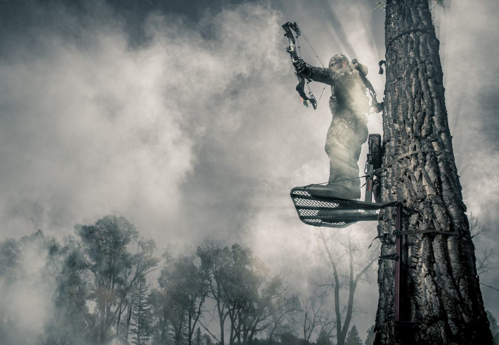This Dramatic Photograph of a Bow Hunter Shooting from a Tree Surrounded by Mist is Part of Walls Product Launch Campaign Photos by Tyler Stableford.