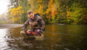 In Clear Cold Water with Fall Colors in the Background, This Triumphant Shot Shows a Woman in Waders with a Cabela's Fly Rod.