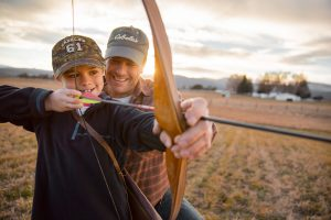 Teaching Hunting Skills to the Next Generation is a Way to Pass On the Outdoor Tradition and This Image of a Father and Son at Sunset Working with a Longbow Captures Those Values.