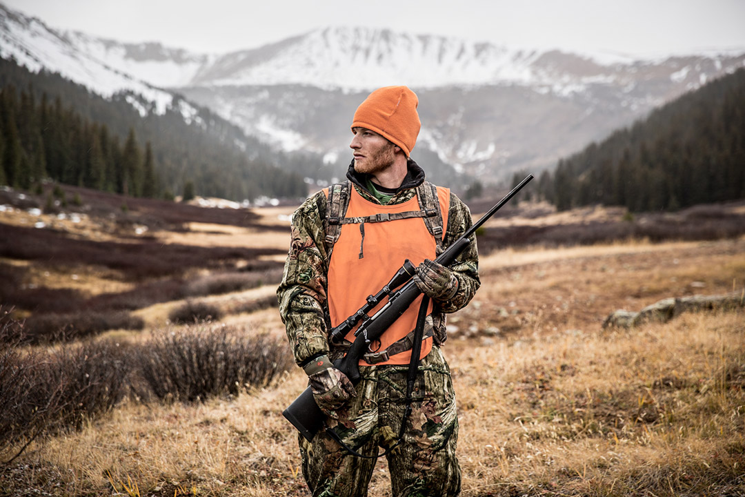 c8fc16065e1b2 Rifle in Hand, this Big Game Hunter Poses in Front of Snow-capped Mountains