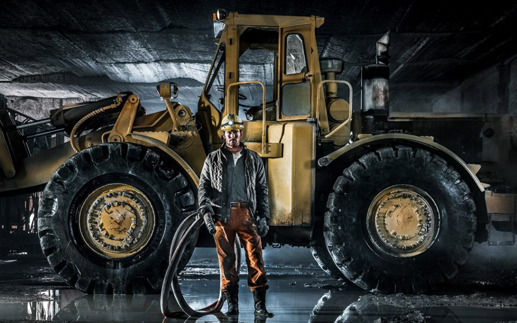 Quarry Worker In Mine Standing In Front Of A Frontloader For Walls Workwear, Dickeys Clothing, Cabelas, Timberland