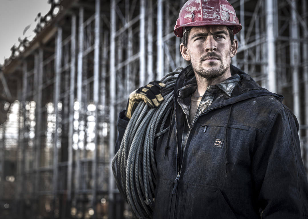 Modern Craftsman Works on a Construction Site while Wearing Heavy Duty Clothing Brands and Safety Gear.