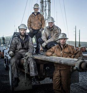 Four Oil and Gas Miners Pose in Work Wear Near their Well-pad in Colorado. All Four Wear Clothing and Footwear Meant for Heavy Industry.