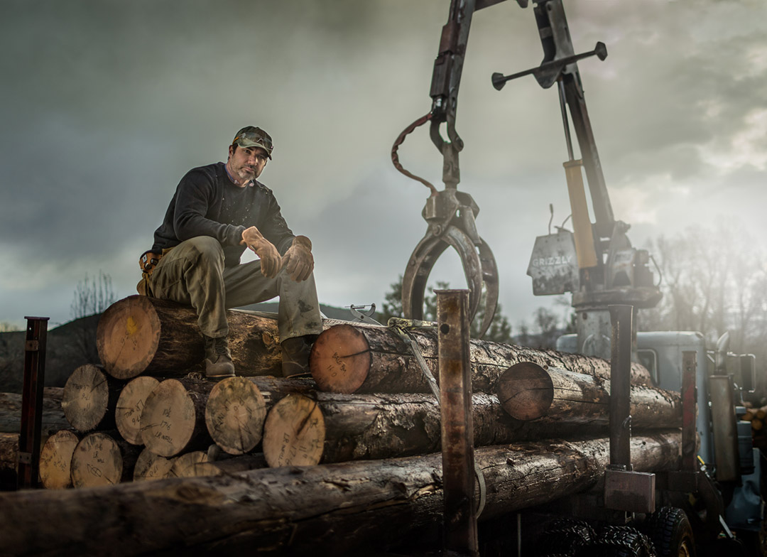 Gray skies frame a modern American worker on the site at a logging development. Portraits like these capture the necessity of tough workwear brands to support these men and women.