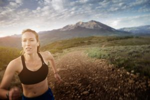 This photo of a Female Long-Distance Runner Shows Rugged Terrain of the Rocky Mountians in the Backdrop. Exercising in the Outdoors is Part of the Colorado Lifestyle.
