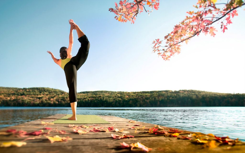 This Fine Art Portrait Shows an Athletic Woman Performing a Yoga Balance Pose on a Floating Dock by a Lake. Yoga is Part of Her Active Lifestyle.