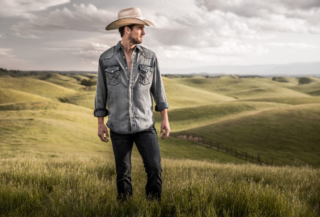 This Cowboy Pic, Taken in a Wide Open Ranchland, Highlights the Jeans, Cowboy Hat, Boots and Denim Shirt of this Unique Lifestyle.