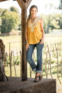 A Lifestyle Portrait of a Young Woman in Western Apparel Posing on a Porch Near a Vineyard.