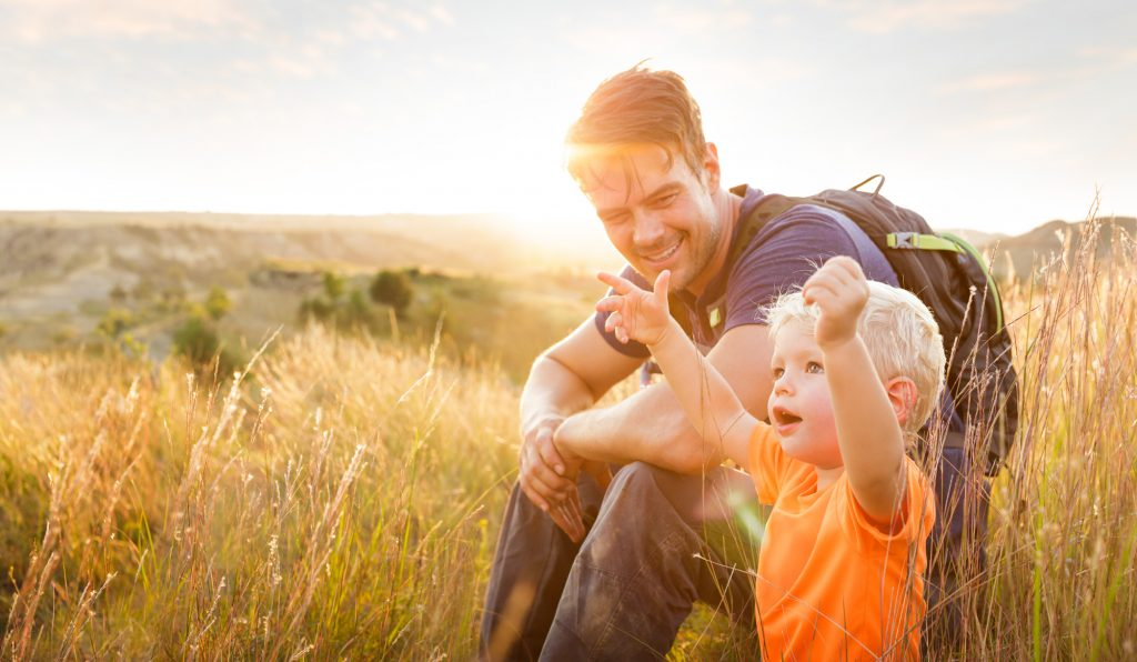 Josh Duhamel sits and smiles at a little boy admiring nature in this sunset photo for North Dakota Tourism, photographed by Tyler Stableford.