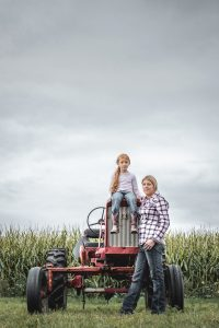 Portrait of mother daughter female farmers with tractor in a corn field.