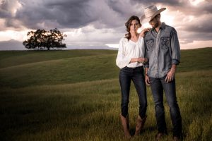 Young Couple Stands In Field Wearing Wrangler Jeans
