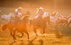 Two Women Ride Horses At Sunset For Wrangler Jenas