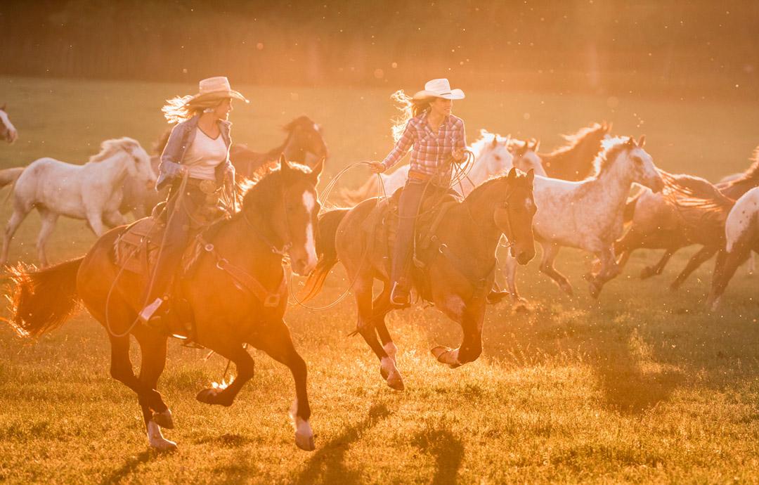 Two Women Ride Horses At Sunset For Wrangler Jenas