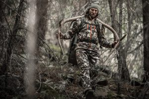 a hunter carrying a rack after field dressing an elk on a big game alpine hunt.