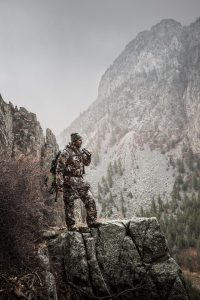 glassing the valley floor, a big game elk hunter in the alpine wilderness