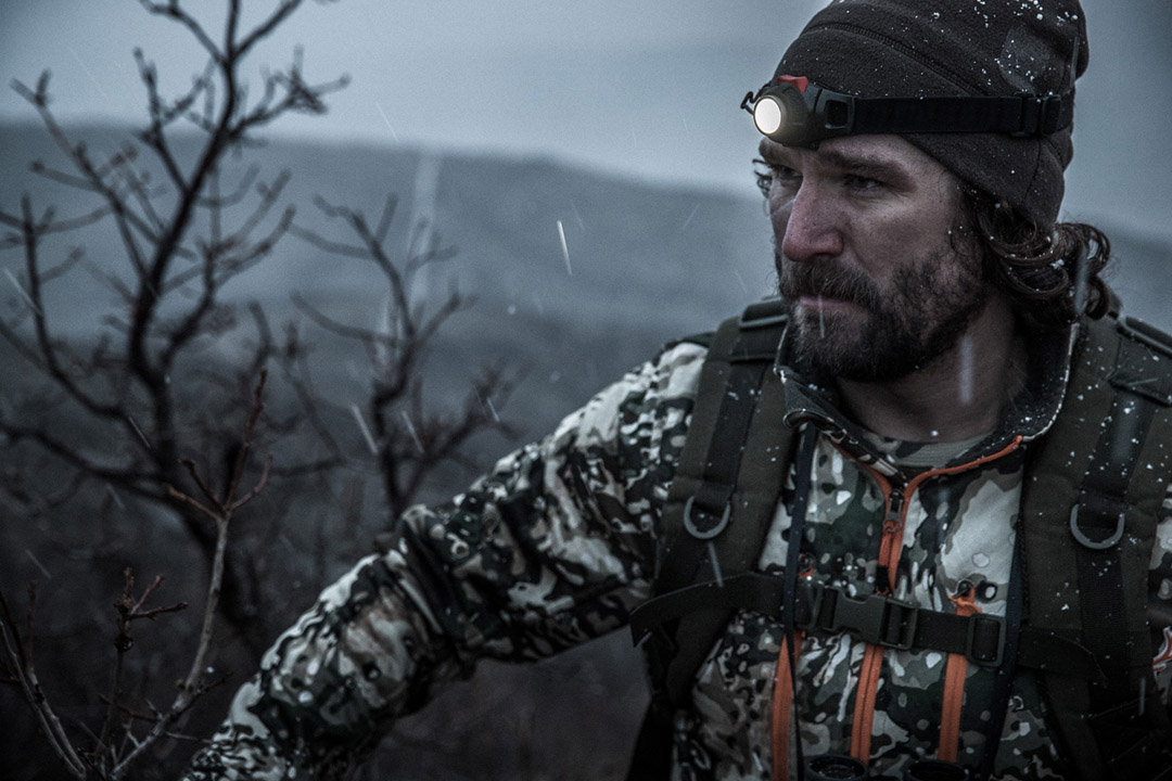 High above tree line, a hunter searches for game as a storm moves in.