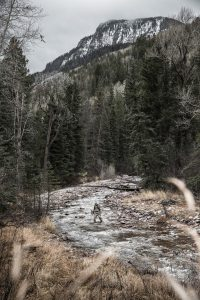 A hunter crosses a frigid high alpine river while bow hunting for elk and other big game.