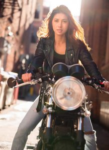 attractive woman on motorcycle wearing vintage leather jacket on the streets of Denver.