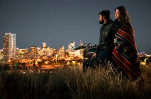 Couple at dusk on motorcycle overlooking the city of Denver.