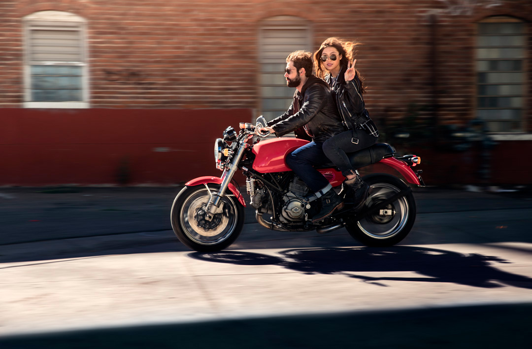 Woman and man riding ducati in the urban streets of Denver for fashion shoot.