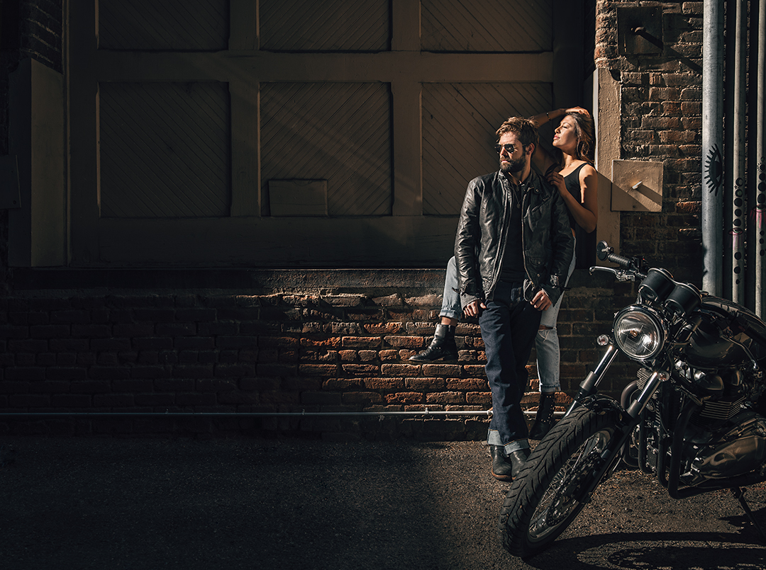 Young urban couple with vintage motorcycle in Denver Colorado.