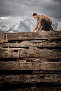 A man makes measurements on a reclaimed beam in Carbondale, Colorado with Mt. Sopris in the background.