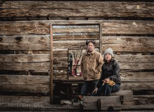 A man and woman take a break from working at a reclaimed timber mill which supplies wood products to Patagonia retail.
