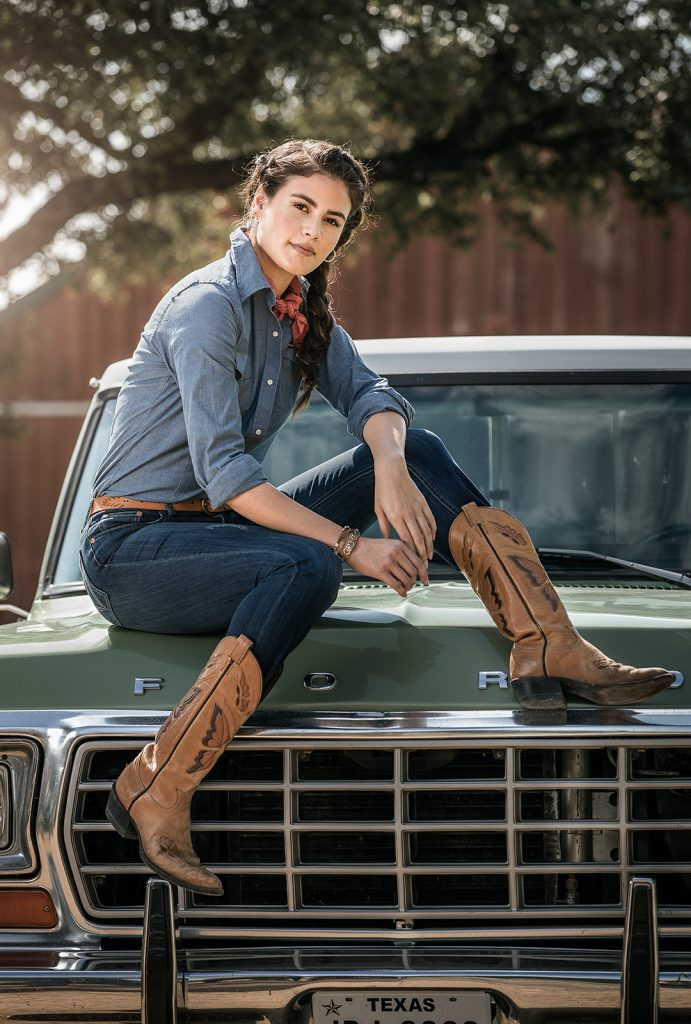 A Wrangler model in denim and cowboy boots sits on the hood of a truck