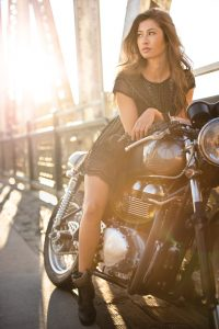 Woman sits on motorcycle, leaning forward and looking off-camera with bright light in background.
