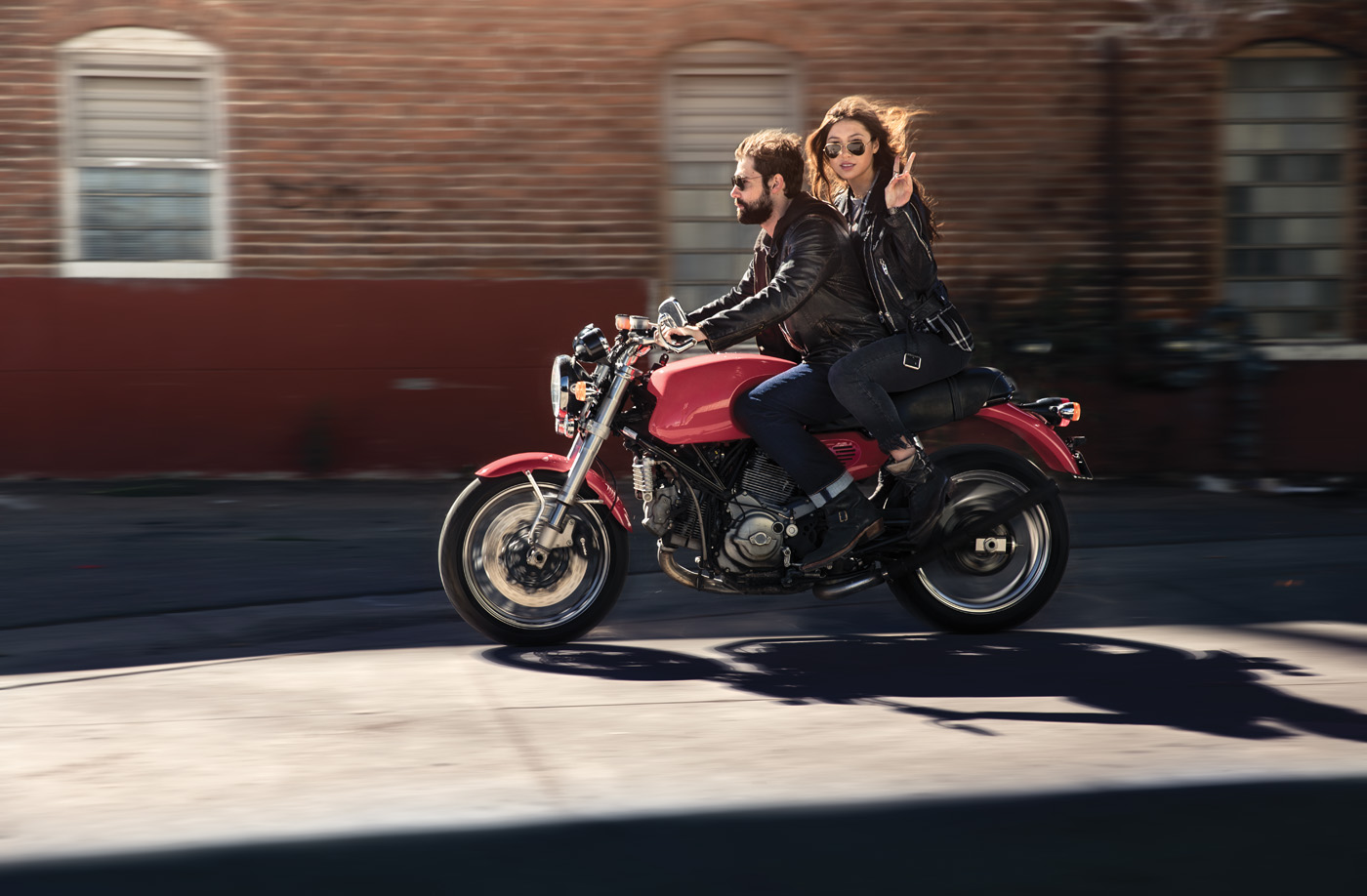 A man drives a red motorcycle while a woman sits behind him and throws up a peace sign.