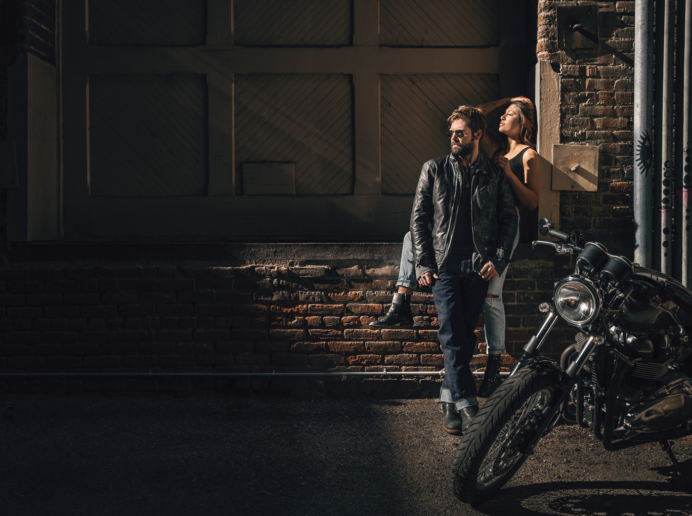 A man and woman lean against brick wall with motorcycle in foreground.